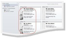 Biznesa kontaktpersonas Outlook kontaktpersonu vizītkartēs; divas biznesa kontaktpersonas ir apvilktas ar sarkanu punktotu līniju.